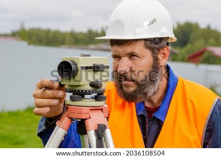 A male engineer works with the optical level on site. A builder in a helmet looks into an optical device. Royalty-Free Stock Photo #2036108504