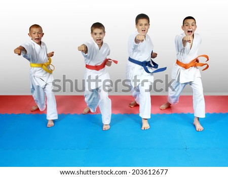 Punch arm in the performance of four athletes in karategi #203612677