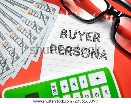 Business concept.Text BUYER PERSONA writing on notepaper with fake money,glasses and calculator on red background.