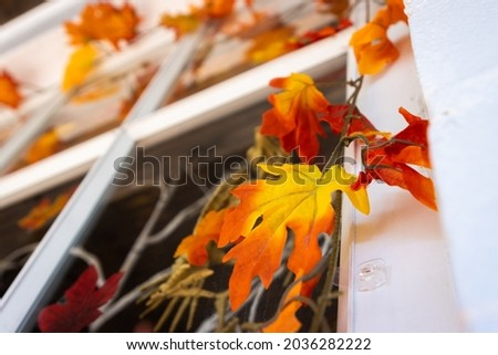 Fall leaves decorating outdoor door of a building. Seasonal photo for autumn, September, October and November. Plastic orange and yellow leaf decorations.