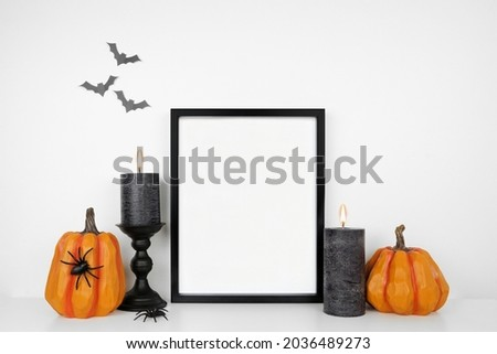Halloween mock up. Black frame on a white shelf with pumpkin decor and black candles. Portrait frame against a white wall with bats. Copy space.