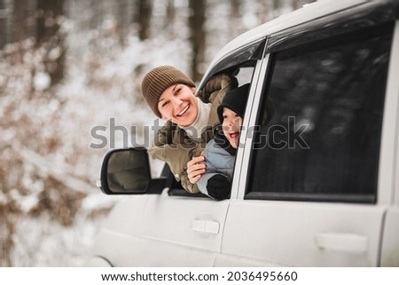 Cheerful adult woman and little boy in outerwear looking at camera while peeking out from vehicle window on blurred background of winter forest Royalty-Free Stock Photo #2036495660