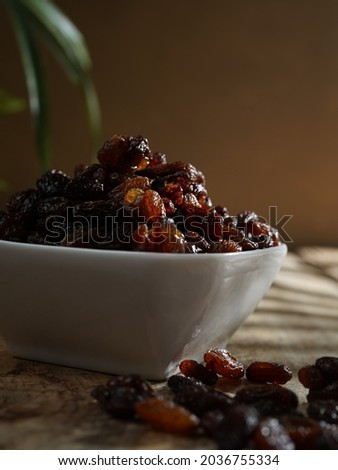 Black raisins in white bowl on wooden table. Raisin black is a color that is a representation of the color of black raisins. Royalty-Free Stock Photo #2036755334