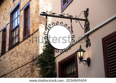 Horizontal front view of empty round signage on a building with classical rustic architecture