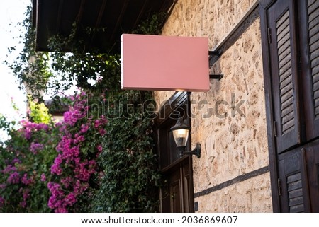 Horizontal front view of empty pink square signage on a building with classical rustic architecture