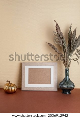 Modern home decor with Pampas grass in vase, mock up beige photo frame and pumpkin, on neutral background. Autumn, fall concept.