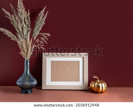 Modern home decor with Pampas grass in vase, mock up beige photo frame and pumpkin, on brown background. Autumn, fall concept.