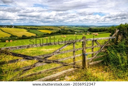 Wooden fence in agricultural land. Farm field fence. Fence in farm field Royalty-Free Stock Photo #2036952347
