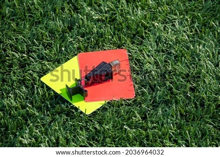Referee soccer, football game whistle, red and yellow cards on green grass. Two penalty cards and a whistle for the referee  F
