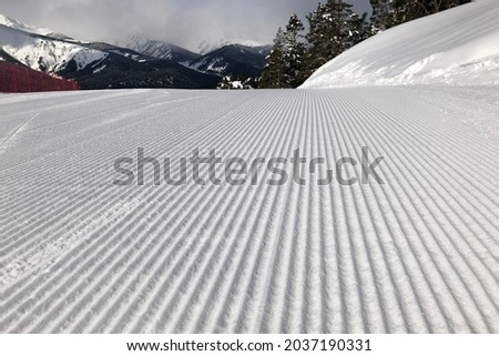 Ski slope prepared for skiing with a snowcat. Velvet shape of groomed slope. Best slope for skiing and snowboarding Royalty-Free Stock Photo #2037190331