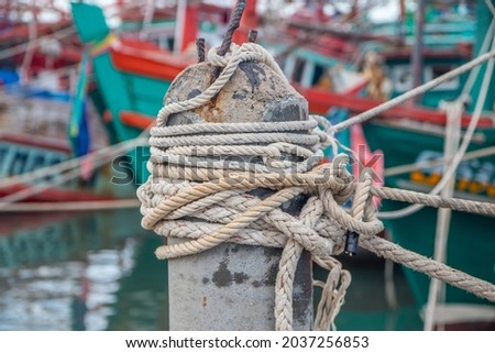 Rope bollard jetty or rope tied up on a pole on a wooden dock or Boat rope tied to a wooden post on a floating boat railing Royalty-Free Stock Photo #2037256853