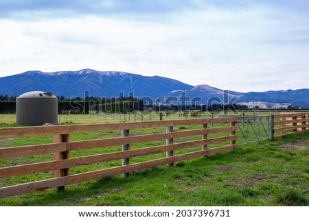 A wooden farm fence with a gate establishes the farm boundary from the country road in Canterbury, New Zealand. A water tank can be seen in the field. Royalty-Free Stock Photo #2037396731