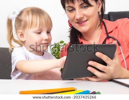 A woman doctor, a pediatrician, shows a 3-4 year old girl cartoons on a tablet. An individual approach to the treatment of each child