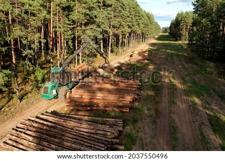 Crane forwarder machine during clearing of forested land. Wheeled harvester transports raw timber from felling site out. Harvesters, Forest Logging machines. Forestry forwarder on deforestation. Royalty-Free Stock Photo #2037550496