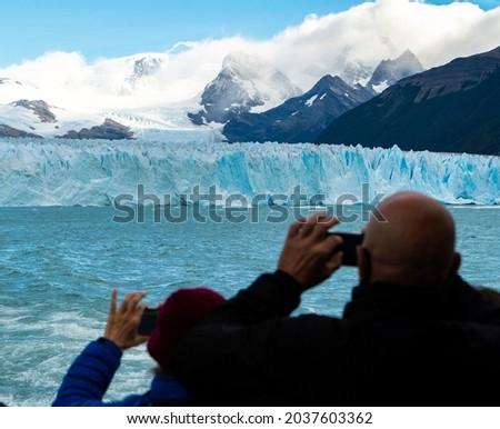 Person from a boat taking a picture of the Perito Moreno glacier.