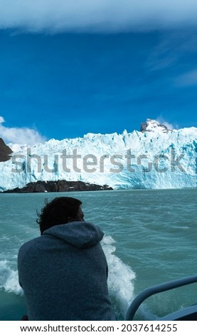 Big Iceberg, people looking at it from the boat, patagonia.