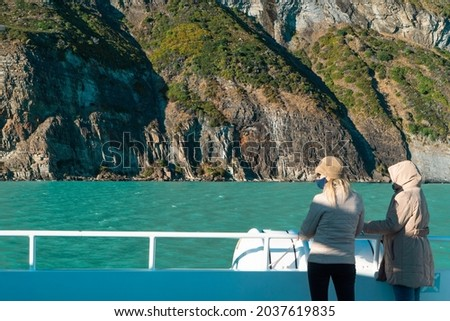 Excursion tourists watching the iceberg from the boat. Perito Moreno glacier in Patagonia. Ice blocks