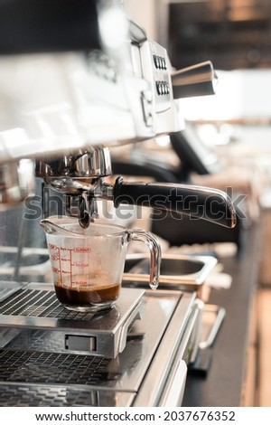 black coffee in measuring cup put on coffee maker
