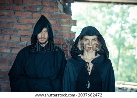 a man and a woman in black raincoats Royalty-Free Stock Photo #2037682472