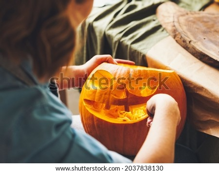 Cropped shot of female carving large orange pumpkin for Halloween party while sitting at wooden table at home, making scary face on jack-o-lantern with knife to set the mood for trick-or-treaters Royalty-Free Stock Photo #2037838130