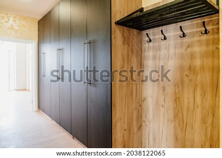 a large spacious wardrobe in the hallway and a hanger for outerwear. classic solution for the interior of the apartment. production of furniture to order. Royalty-Free Stock Photo #2038122065