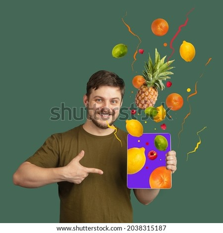Contemporary artwork of smiling caucasian man pointin on tablet screen and doing online grocery shopping isolated over green background. Tropical fruits flying out tablet. Buying food from home, ad