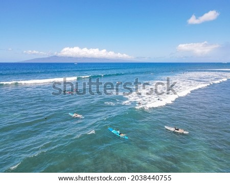 Aerial pic of surfers seating on surfboards and waiting for wave in the middle of ocean with perfect weather and clean water in Hawaii paradise, shot on drone from above