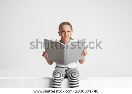 Fairy tail. Portrait of cute Caucasian girl, teen sitting and reading big book, magazine isolated on gray studio background. Happy childhood, education, emotion, facial expression concept.
