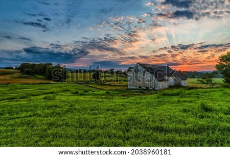 Morning dawn over a farm in a field. Valley farm at dawn. Sunrise over farm field. Early morning farm field at dawn Royalty-Free Stock Photo #2038960181