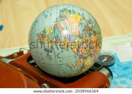 an old camera on a geographical map of the world instead of a globe lens the concept of travel tourism. High quality photo Royalty-Free Stock Photo #2038966364