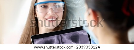Dentist holding digital tablet with 3D picture of teeth in hands in front of female patient