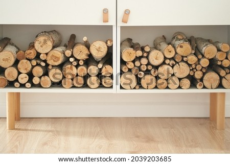 Stocks of firewood for the fireplace are stacked on the shelves. Background of dry chopped wood logs in a pile, on a white shelf. High quality photo