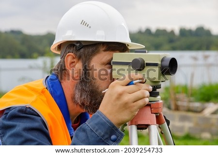 A male engineer works with the optical level on site. A builder in a helmet looks into an optical device. Royalty-Free Stock Photo #2039254733