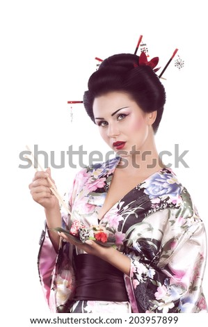 Young woman in Japanese kimono with chopsticks and sushi roll, isolated on white background. #203957899