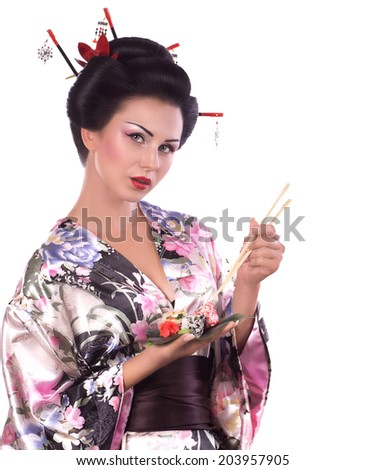 Young woman in Japanese kimono with chopsticks and sushi roll, isolated on white background. #203957905
