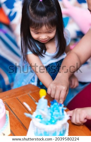 Vertical image. Portrait of a cute Asian girl cutting a blue cake celebrating her 4th birthday, with her mother's hand holding her hand holding a cake knife.