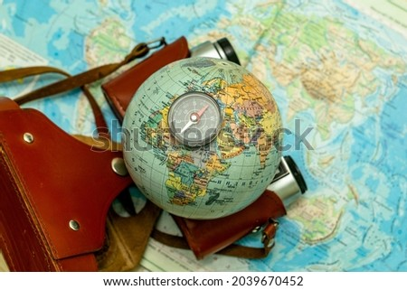an old camera on a geographical map of the world instead of a globe lens the concept of travel tourism. High quality photo Royalty-Free Stock Photo #2039670452
