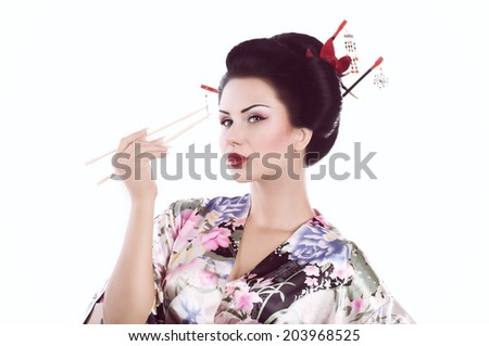 Young woman in Japanese kimono with chopsticks and sushi roll, isolated on white background. #203968525