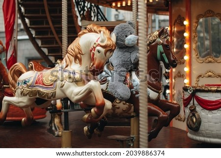 Children ride horses and teddy bear in protective mask on children's carousels in an amusement park.