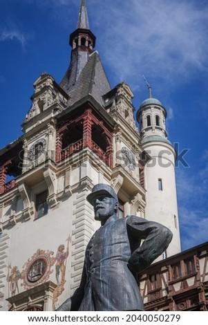 Stone statue King Carol 1 and clock tower at Peles castle royal palace, Romania