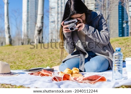 Young adult Latina girl sitting on picnic blanket taking a picture with her camera of the food she has brought with her. Concept of photography and picnic.