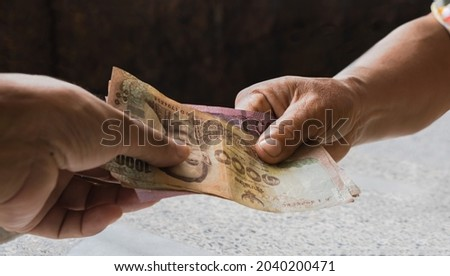 hand holding money banknote thai baht, giving and receiving money concept, (savings, shopping, pay, borrow), hand holding paper money close-up Royalty-Free Stock Photo #2040200471