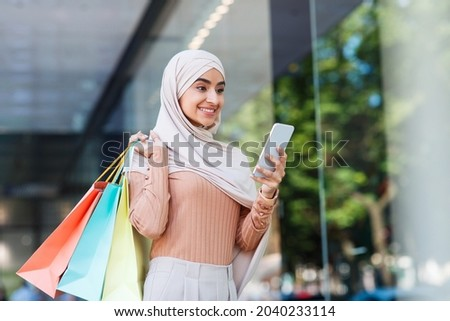 Satisfied cute young middle eastern female in hijab with many packets, texting message on smartphone near mall, enjoy shopping and sale, empty space. Fashion lifestyle, discounts in mobile application Royalty-Free Stock Photo #2040233114