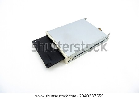 Internal FDD 3.5-inch floppy disk drive for PC, a 1.44 Mb floppy disk is inserted into it, isolated on a white background. Floppy Disk Drive