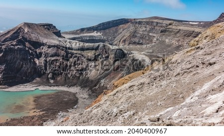 The caldera of an active volcano. The structure of the steep slopes of the crater is visible. At the bottom is a turquoise acid lake with melted snow on the banks. Blue sky. Kamchatka. Uzon Royalty-Free Stock Photo #2040400967