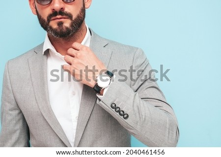 Closeup portrait of handsome confident stylish hipster lambersexual model.Sexy modern man dressed in elegant suit. Fashion male posing in studio near blue wall in sunglasses Royalty-Free Stock Photo #2040461456