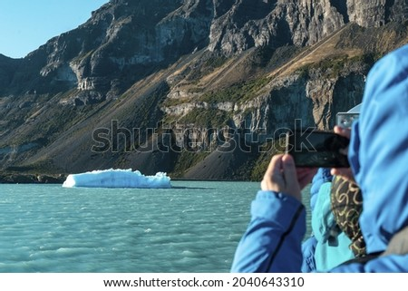 Big Iceberg, people looking at it from the boat, patagonia