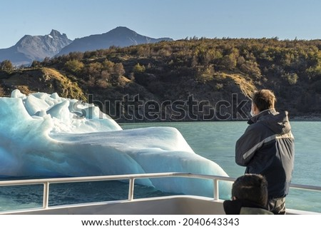 Excursion tourists watching the iceberg from the boat  Perito Moreno glacier in Patagonia  Ice blocks