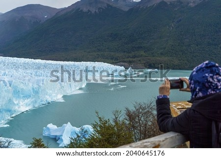 On the walkways of the glacier the woman takes pictures of the glacier