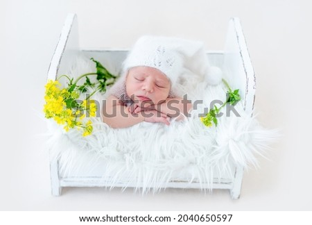 Adorable newborn baby boy sleeping on his tummy in white wooden bed with yellow flowers. Cute infant kid wearing knitted hat napping during studio photoshoot Royalty-Free Stock Photo #2040650597